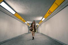 beautiful young woman posing in a subway underpass - stock photo