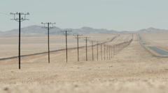 Endless road and electricity poles to horizon in desert of Namibia Stock Footage