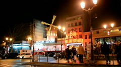 Red windmill (Moulin Rouge) cabaret at night in Paris, France. Stock Footage