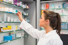 Stock Photo of Junior pharmacist taking medicine from shelf