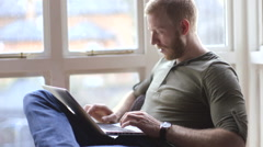 Young man working from home on his laptop Stock Footage