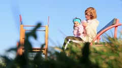 Mother with A Little Baby In Her Arms Sitting On The Bench In The Park - stock footage