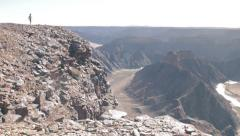 Person walks towards edge of cliff of Fishriver canyon in Namibia, dolly move Stock Footage