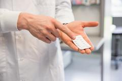 Pharmacist holding medicine blister pack - stock photo