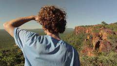 Young man overlooks vast mountain and forest range of Waterberg plateau, Namibia Stock Footage