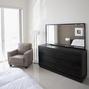 Sofa, dresser and mirror in modern apartment Stock Photos