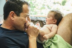 Caucasian father kissing feet of baby boy Stock Photos
