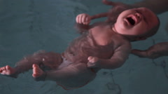 Baby 3 months learn to swim in the pool Stock Footage