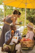 Vendor showing produce to girl at farmers market Stock Photos