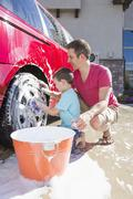 Caucasian father and son washing car in driveway Stock Photos