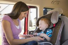 Caucasian mother fastening son into car seat Stock Photos