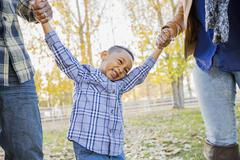 Black family playing in autumn leaves Stock Photos