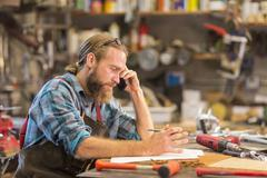 Caucasian craftsman working in workshop Stock Photos