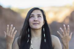 Mixed race woman meditating in desert Stock Photos