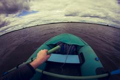 Caucasian girl rowing canoe on lake Kuvituskuvat