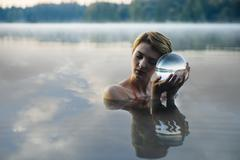 Caucasian woman holding crystal ball in still lake Stock Photos