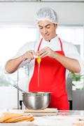 Chef Breaking Egg In Mixing Bowl While Preparing Pasta Stock Photos
