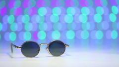 Retro sunglasses as travel concept on a blurry colorful background Stock Footage