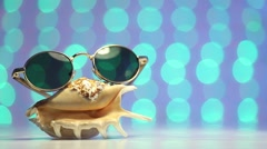 Shell and sunglasses as travel concept on a blurry colorful background Stock Footage