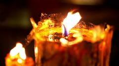 Burning candle in temple close up with wax texture and glow Stock Footage