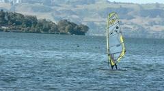 Person windsurfing over Lake Rotorua and Rotorua cityscape New Zealand 01 Stock Footage