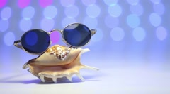 Shell and sunglasses as travel concept on a blurry colorful background - stock footage