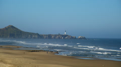 View of Yaquina Head Lighthouse from beach, Newport Stock Footage