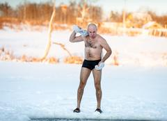 man wipes towel after swimming in  freezing - stock photo