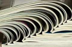 pile of colorful magazines on a table - stock photo