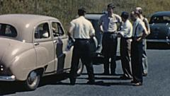 England 1955: men talking in the street outside their cars Stock Footage