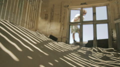 Sand filled abandoned house with man in desert ghost town Kolmanskop, Namibia Stock Footage
