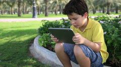 Young boy gaming on tablet computer - stock footage