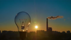 The incandescence bulb by the industrial city background. Time lapse shot Stock Footage