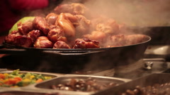 Meat is fried on a big frying pan at street fair Stock Footage