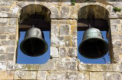 Stock Photo of ancient bell tower with bells and blue sky