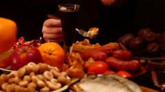 Man eats at the table, different food on black background 4k Stock Footage