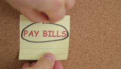 Pay bills note on a bulletin board Stock Footage