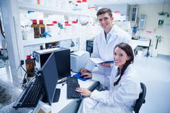 Chemist team working together at desk using computer - stock photo