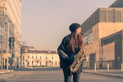 Beautiful young woman playing tenor saxophone Stock Photos