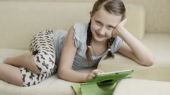 Innocent blonde ponytail white skin girl playing using tablet lie on cream couch - stock footage