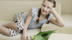 Little blonde ponytail white skin girl playing using tablet lie on cream sofa Stock Footage