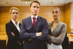 Three serious lawyers standing with arms crossed - stock photo