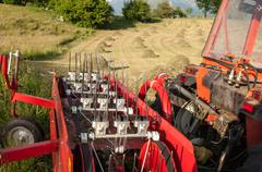 Detail of a tractor in front of hay bales during the works of autumn season Stock Photos