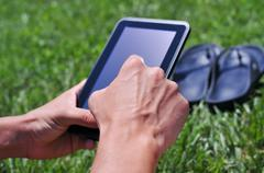 Young man using a tablet computer in a park Stock Photos