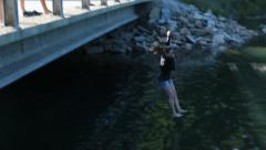 Woman jumps off bridge into river - stock footage