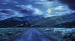 abandoned road through meadows in mountain at night - stock photo