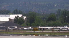 Aircraft, unmarked commuter jet taxis past aircraft, long shot, nice heat Stock Footage
