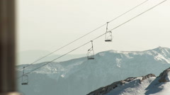 Stock Video Footage of Empty Ski Lift Riding Up And Down Above Mighty Mountain Peaks On Winter Day