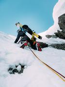 Stock Photo of ice climbing: mountaineer on a mixed route of snow and rock during the winter