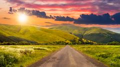 Abandoned road through meadows in mountain at sunset Stock Photos